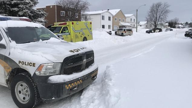 Trois voitures de la Sûreté du Québec et une ambulance sont stationnés sur une rue enneigée.