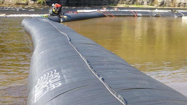 Des travailleurs installent une barrière anti-inondations dans un endroit submergé d'eau.