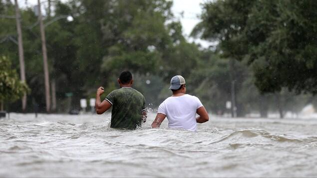 Deux hommes marchent dans une rue, ils ont de l'eau jusqu'à la taille.
