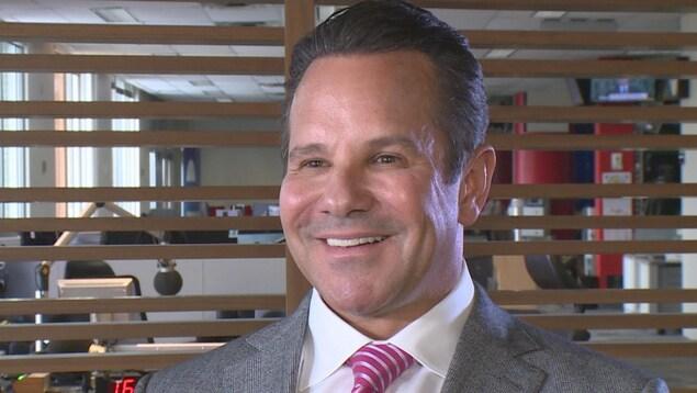 Un homme en complet-cravate sourit à la caméra.