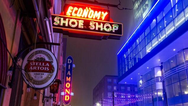 Enseigne du Economy Shoe Shop au-dessus d'une rue piétonnière enneigée.