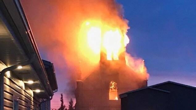 Le clocher est engouffré par les flammes