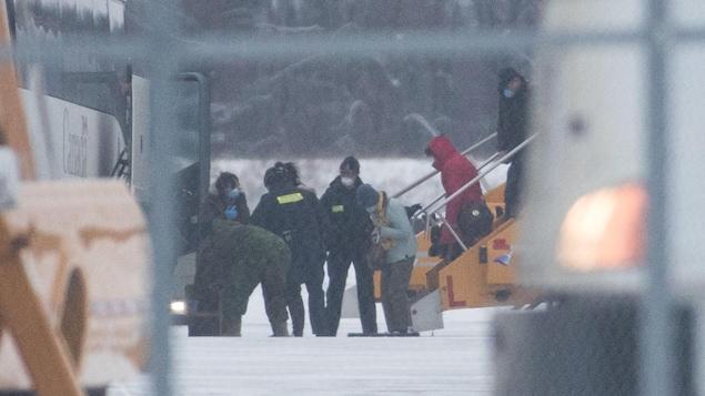 Les Canadiens évacués de Wuhan, en Chine, descendent de l'avion qui les a conduits à Trenton, en Ontario.