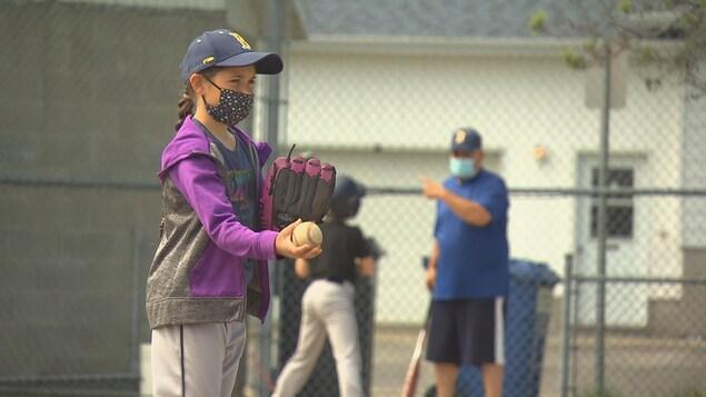 Une jeune qui tient une balle de baseball et qui s'apprête à lancer sur le terrain.