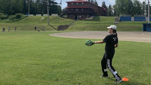Une jeune fille sur le terrain de baseball.