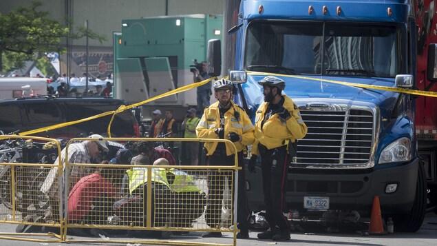Des policiers et des passants s'occupent d'une personne couchée dans la rue, près d'un camion.