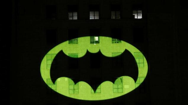Un logo de chauve-souris est projeté sur la façade d'un édificie.