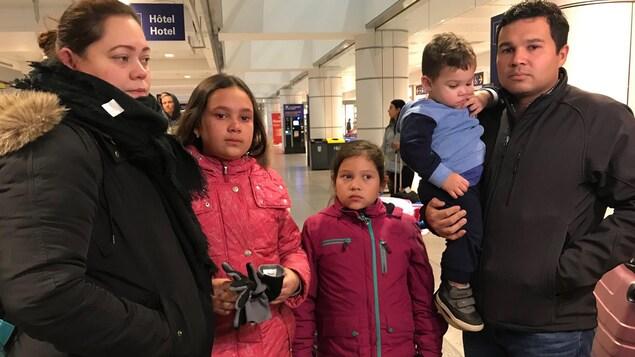 La famille, composée des parents et de trois enfants, le regard triste, attend de prendre l'avion à l'aéroport
