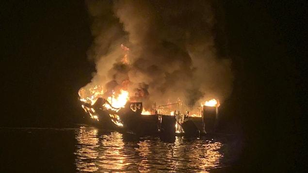 Le bateau en flammes pendant la nuit.