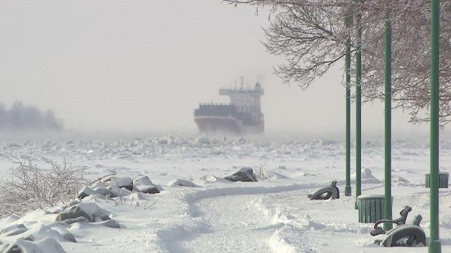 Un bateau, vu de la berge, navigue sur les eaux glacées du fleuve Saint-Laurent.