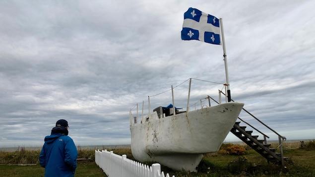 Un homme regarde au large à la hauteur de Pointe-au-Père dans le Bas-Saint-Laurent. À sa droite se trouve un bateau et un drapeau du Québec qui flotte.