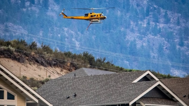 A helicopter flies over homes in the Oliver, B.C., area on Monday to help fight the wildfire known as the Nk'Mip fire, which forced dozens of evacuations.