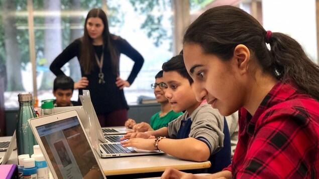 Une jeune fille regarde un ordinateur dans une classe.