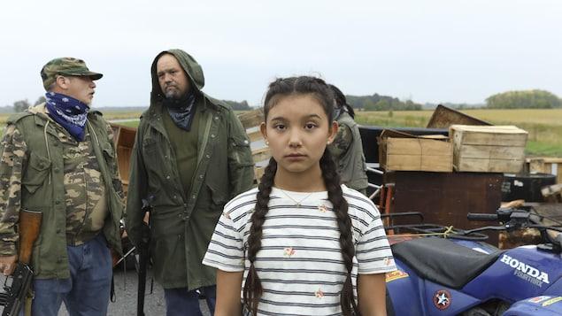 Une jeune fille avec de longues tresses en premier plan. Derrière elle, deux hommes discutent.