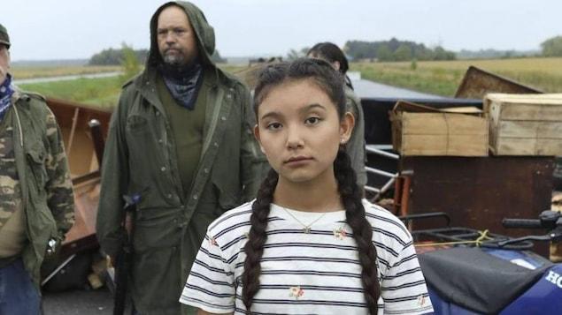 Une jeune fille regarde dans la caméra. Trois personnes vêtues d'imperméables sont en arrière-plan.