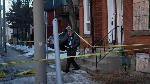 Un détective quitte une résidence où une enquête est en cours.