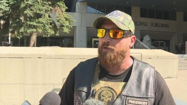Un homme barbu avec une casquette et des lunettes de soleil