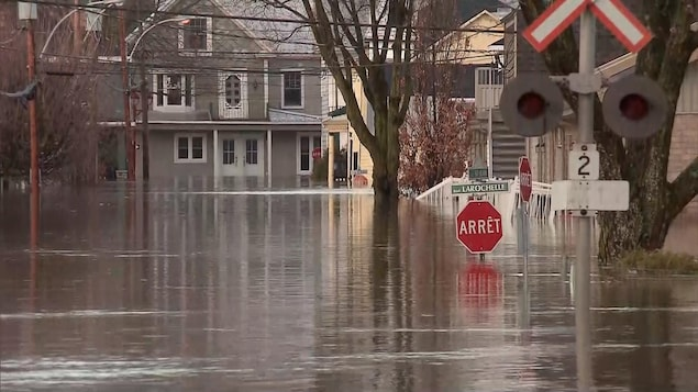 De l'eau monte jusqu'au niveau des panneaux de signalisation