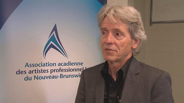 Philippe Beaulieu en entrevue devant une affiche de l'Association.