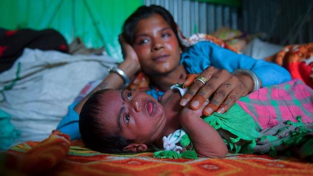 Une mère indienne est couchée près de son bébé.
