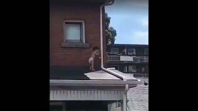 Un bébé debout sur un toit.