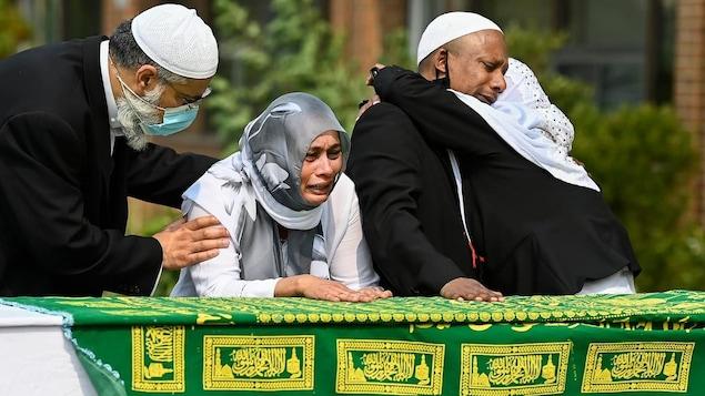Quatre personnes devant un cercueil