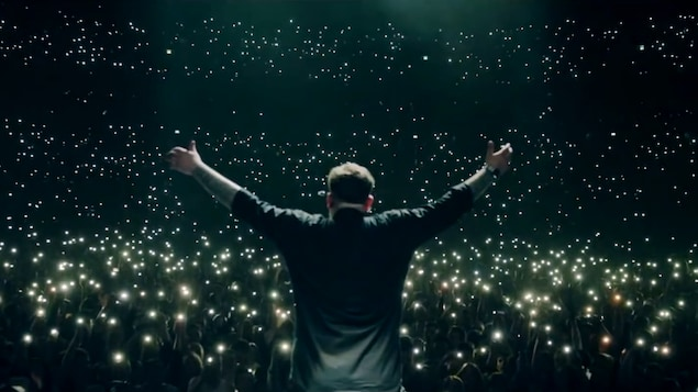 Un artiste sur scène, vu de dos, devant les lueurs des centaines de téléphones du public.