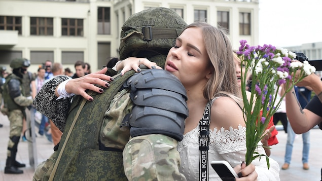 Une jeune femme tenant des fleurs serre un policier dans ses bras.