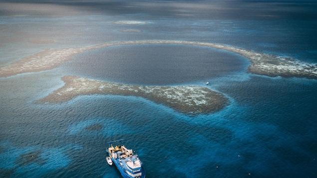 Vue du ciel de la barrière de récif qui forme un cercle de rochers et de sable.