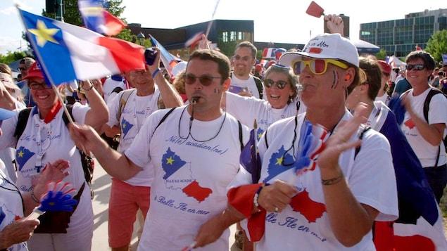 Des Bellilois, sifflets à la bouche, portant des chandails de l'Acadie et agitant des drapeaux de l'Acadie.