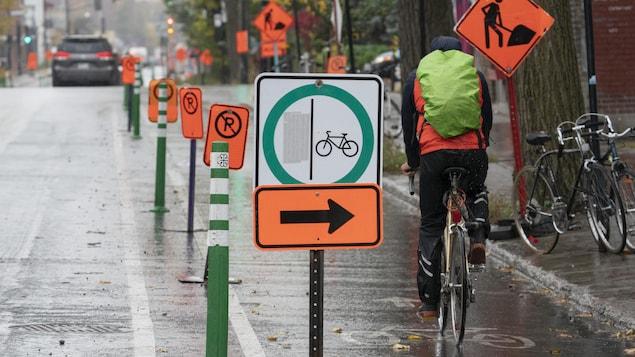 Un cycliste roule sur une piste cyclable à Montréal.