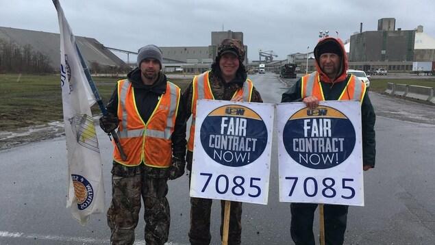 Trois hommes portant des pancartes et un drapeau syndical devant l'usine