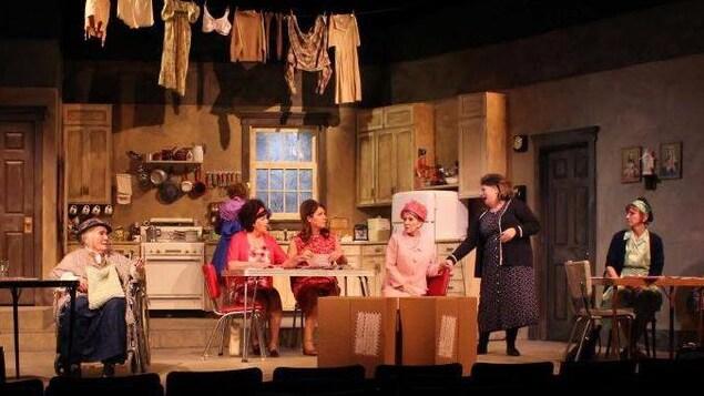 Neuf actrices, toutes blanches, jouent une scène de la pièce de théâtre « Les Belles-soeurs ».