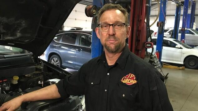 Jean-Paul Belliveau inspecte le moteur d'une voiture