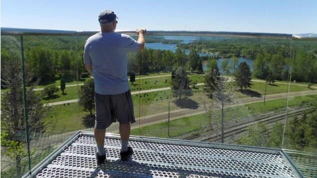 Un homme regarde au loin sur un belvédère.
