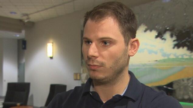 Portrait d'un homme aux cheveux bruns coupés courts qui regarde le journaliste; en arrière-plan on distingue un tableau accroché à un mur et des  sièges noirs.