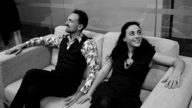 Ben Liegey et Laure Dupuy, assis sur un canapé côte à côte, regardant chacun dans une direction opposée.