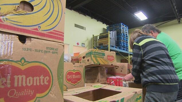 Des bénévoles s'affairent dans un entrepôt d'aide alimentaire