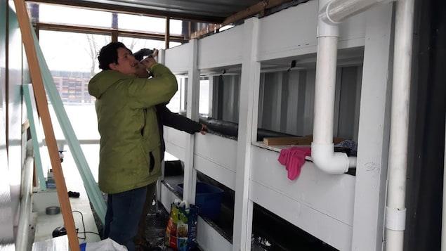 Benjamin Laramée travaille sur l'isolation des conteneurs qui formeront la ferme aquaponique.
