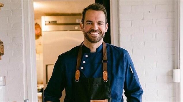 Un chef avec son tablier dans une cuisine.