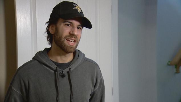 Benjamin Proulx se tient debout devant une caméra lors d'un entretien.