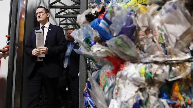 Le ministre de l'Environnement, Benoit Charette et des matières recyclables dans un centre de tri.