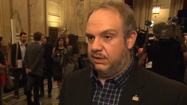 Benoit Dorais, maire de l'arrondissement du Sud-Ouest, en point de presse à l'hôtel de ville, avec un groupe de personnes en train de discuter à l'arrière.