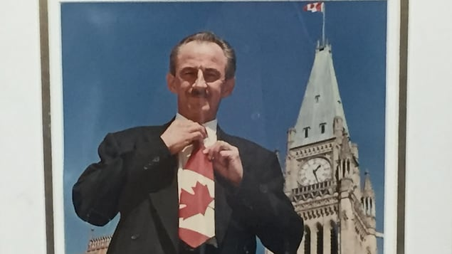 Une photo d'un homme debout devant le Parlement canadien