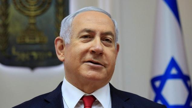 Le premier ministre israélien Benyamin Nétanyahou est photographié devant un drapeau d'Israël.