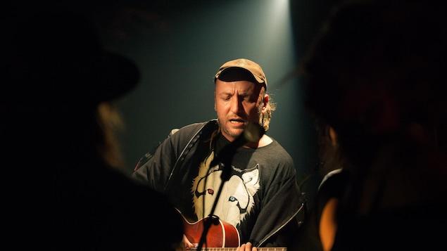 Un homme en concert avec sa guitare sur scène.