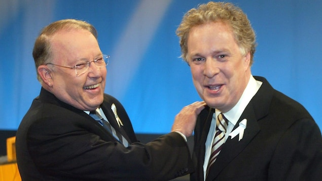 Les deux hommes rient de bon coeur.