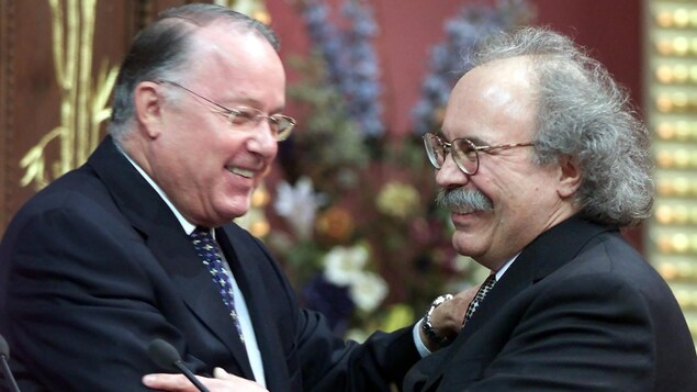 Les deux hommes se font l'accolade en souriant.