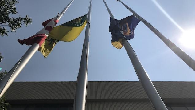 Trois drapeaux sont en berne, la prise de photo de caméra est de haut, et on voir le ciel.