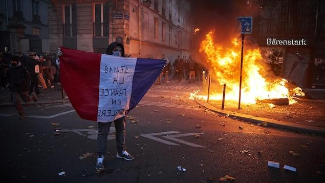 Un jeune homme porte un drapeau tricolore non loin d'un pneu qui brûle.